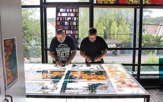 Zwei Männer die an einem Leuchttisch Glasmalereien kontrollieren